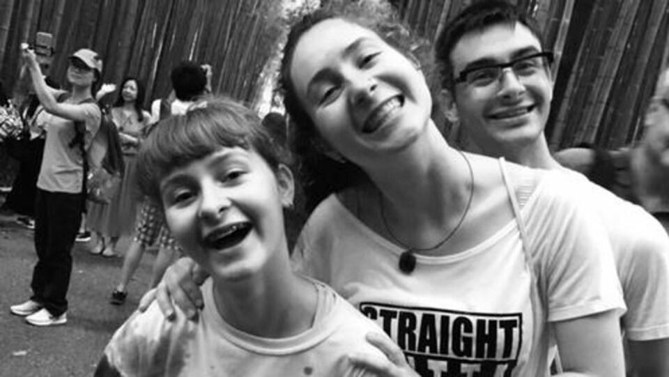 Trois ados posent pour la photo en souriant. Derrière eux, on voit des bambous et des touristes. La photo est en noir et blanc.