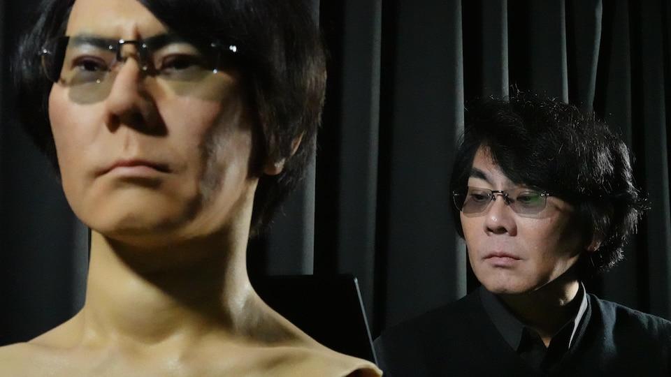 Hiroshi Ishiguro et son plus récent double : Geminoid Hi-5, sur fond noir.