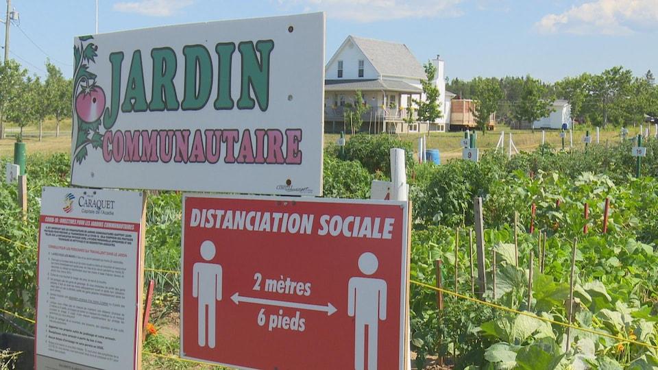 Une affiche indique l'entrée du Jardin communautaire de Caraquet, jumelée à une affiche indiquant le respect des consignes de distanciation sociale.