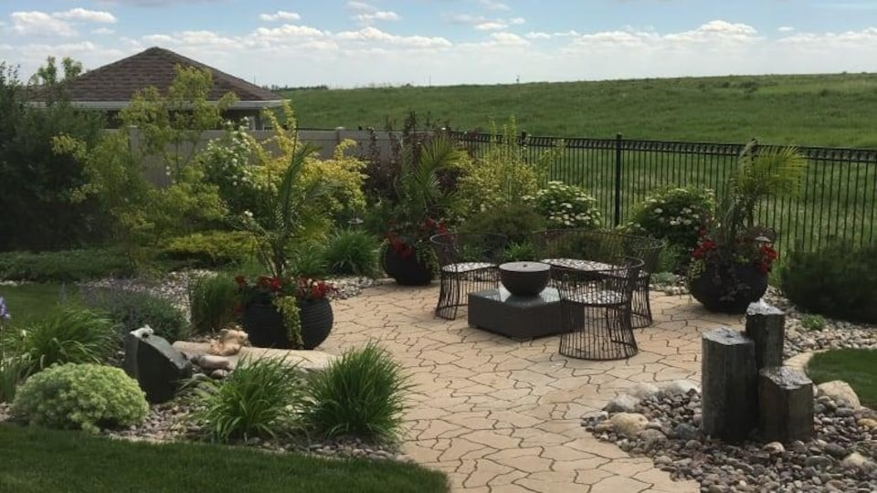 Une cour intérieure avec  plusieurs types de plantes, revêtementen pavé et mobilier de jardin.