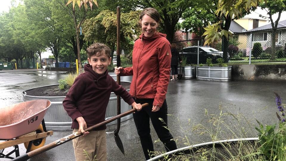 Theo et Alison, avec chacun une pelle à la main, derrière une jardinière.