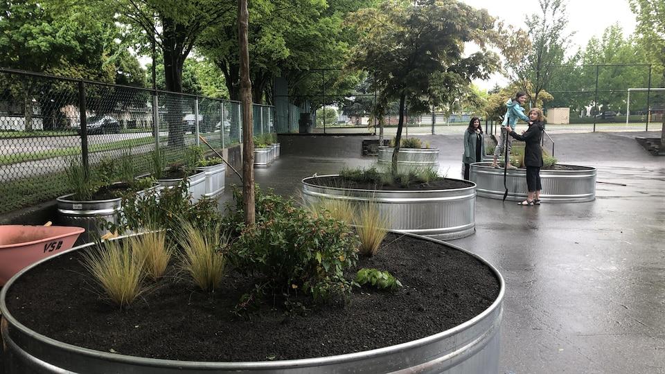 Vue d'ensemble sur les cinq grosses jardinières rondes et les petites jardinières ovales.