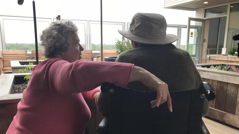Un couple de personnes âgées, de dos, sur une terrasse de toit.
