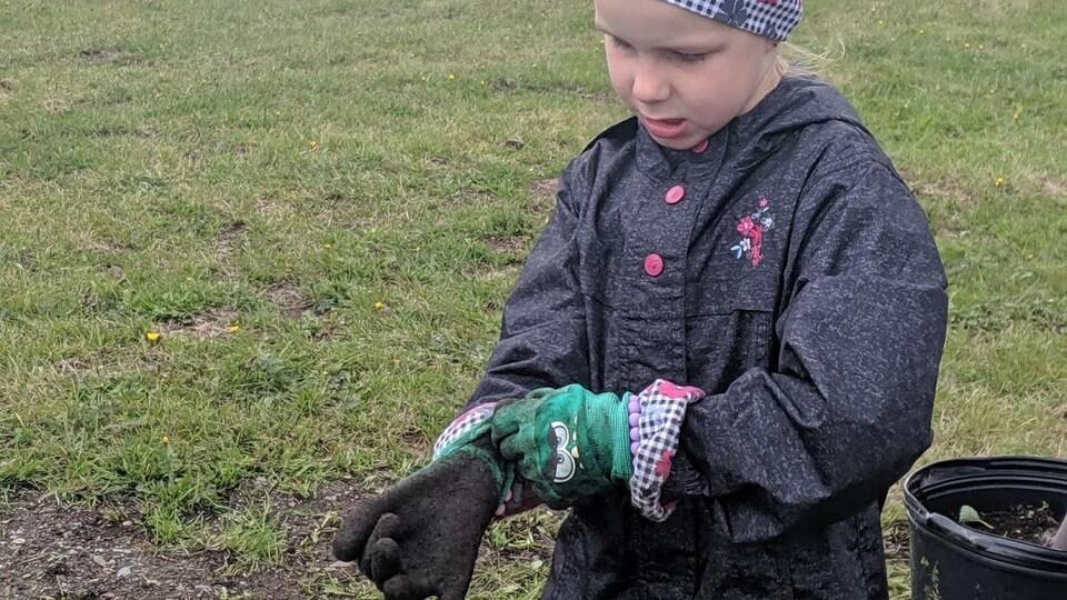 Une fillette met des gants de jardinage pleins de terre.