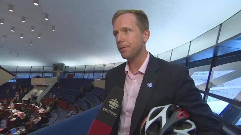 Un homme en entrevue avec un casque de vélo sous le bras.
