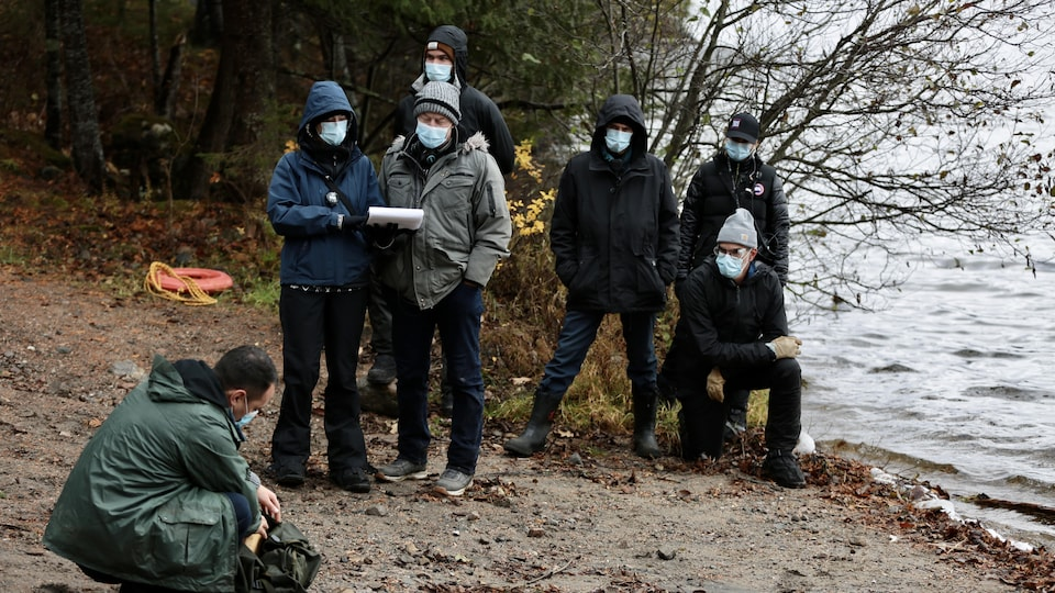 Une équipe de tournage vêtue de vêtements foncés portent des masques et sont installés en bordure d'un point d'eau.