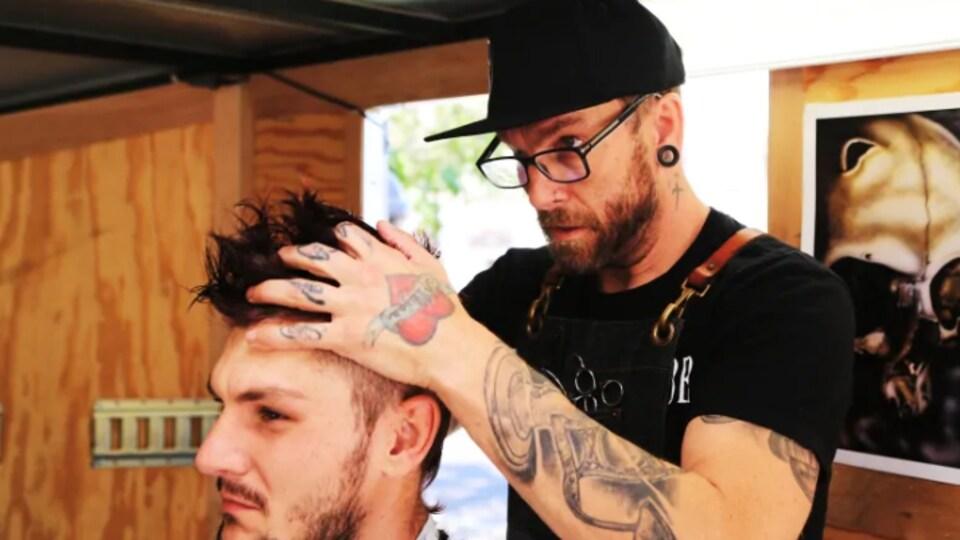 Un homme est en train de couper les cheveux à un client.