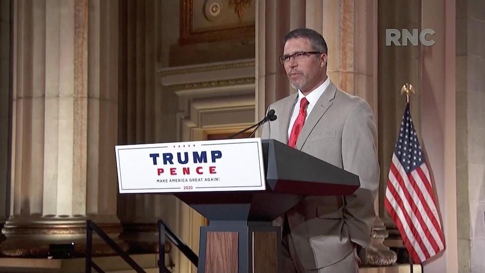 Jason Joyce devant un podium auquel est fixé une affiche Trump-Pence 2020.