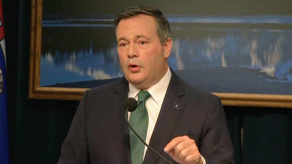 Jason Kenney parle à un podium dans une salle du gouvernement albertain.