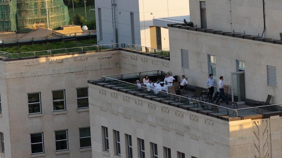 Six personnes mangent à une table ronde sur une terrasse, alors que deux serveurs débarrassent la table.