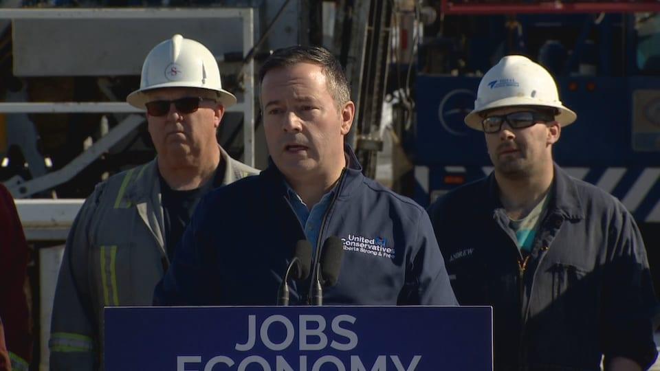 Jason Kenney au podium lors d'une conférence de presse, devant deux travailleurs d'usine.
