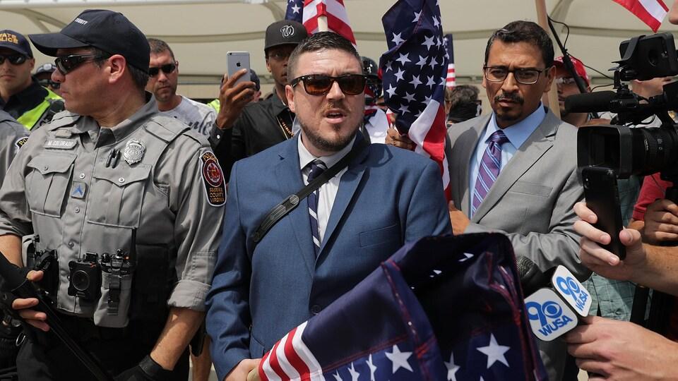 Un jeune homme aux cheveux courts et portant un veston et une cravate ainsi que des lunettes de soleil transporte un drapeau américain sous escorte policière. Une caméra de télévision est braquée sur lui.