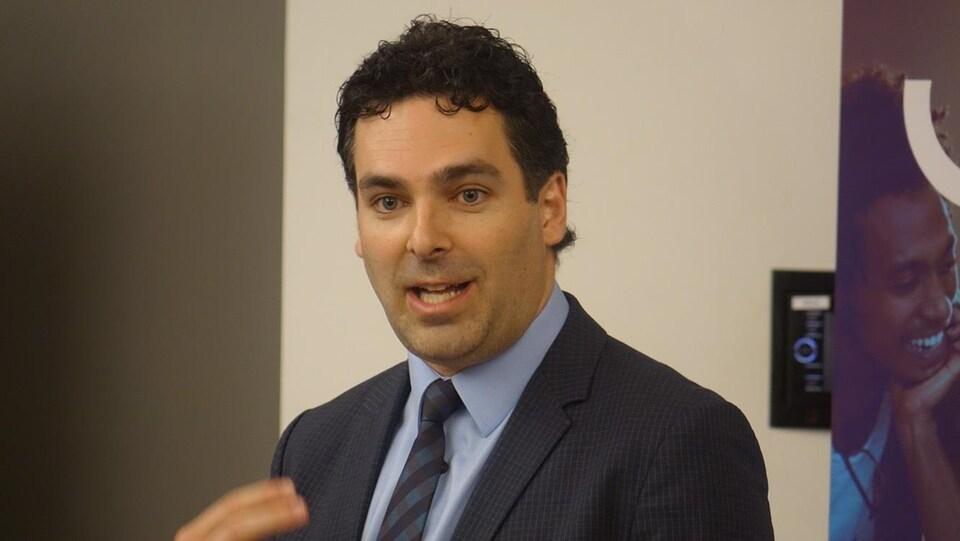 Jason Luckerhoff, vice-recteur au développement des programmes de l'Université de l'Ontario français parle devant un micro lors d'une conférence de presse.