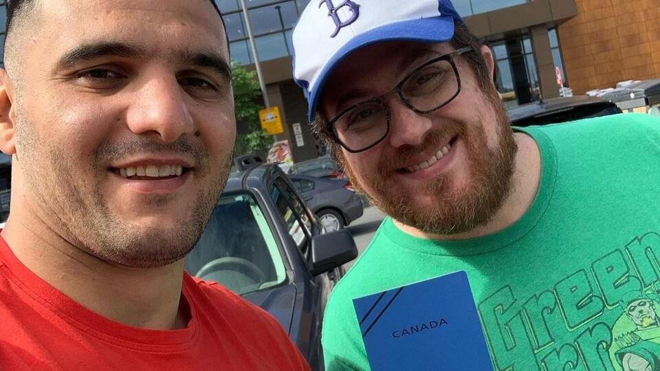 Javad Mahjoub est accompagné de son ami Robbie Stein qui tient un document de voyage du Canada dans sa main.
