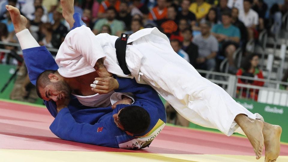Le judoka est dos au sol avec son adversaire sur lui.