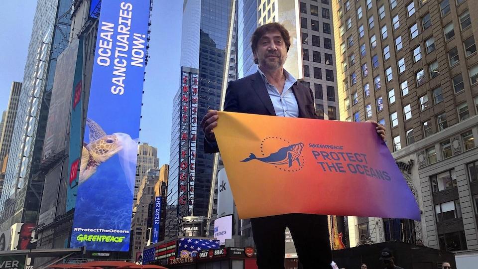 L'acteur tient entre ses mains une banderole sur laquelle on peut lire : « GREENPEACE / PROTECT THE OCEANS ».