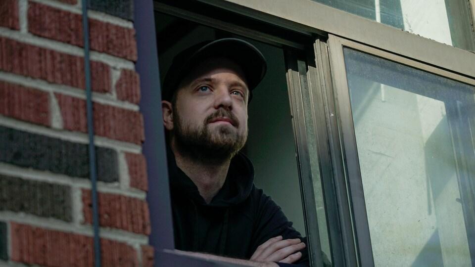 Un homme regarde par la fenêtre.