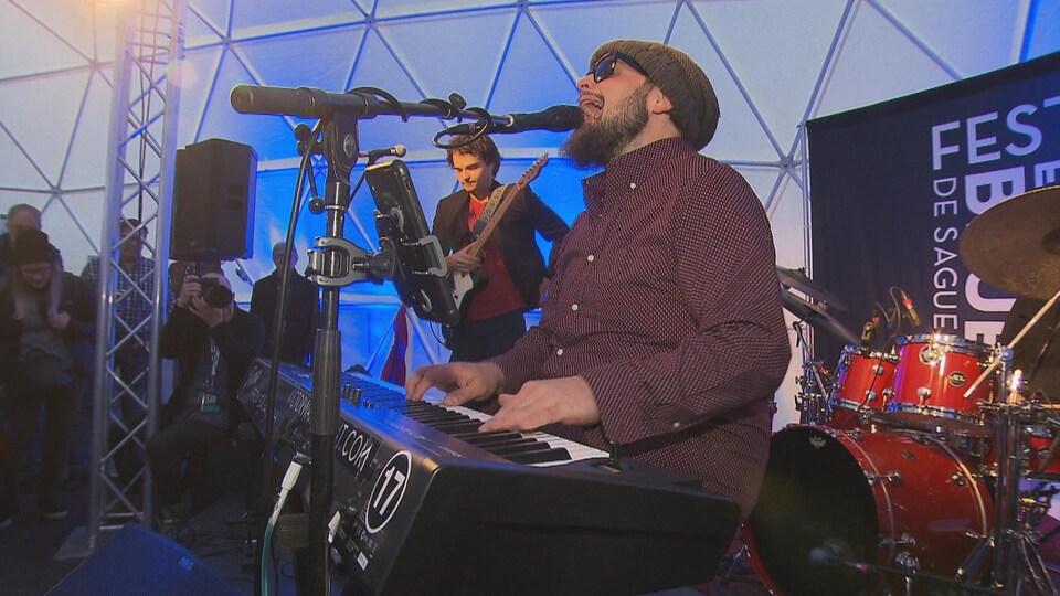 Un homme joue du piano entouré des autres membres de son groupe.