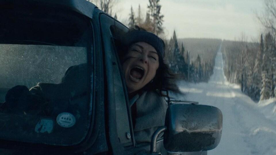 Une femme conduit sur une route eneigée. Elle cri par la fenêtre.