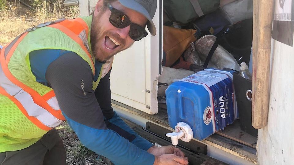 Jean-Baptiste Larocque se lave les mains à partir d'un bidon d'eau placé à l'arrière d'un véhicule.