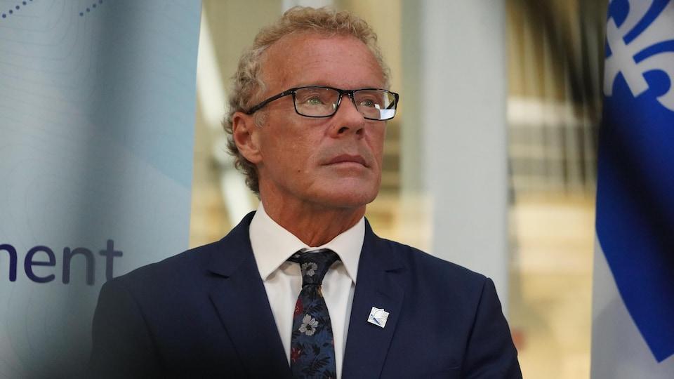 Le ministre Boulet debout, près d'un drapeau du Québec.