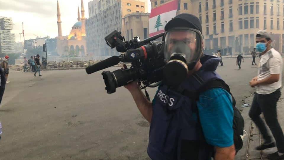 Un homme tenant une camera et portant un masque à oxygène dans la place publique à Beyrouth.