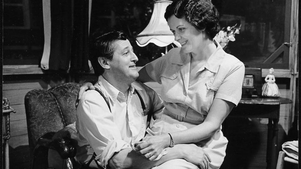 La comédienne Louise Rémy est assise sur les genoux de Jean Brousseau, qui la tient dans ses bras.