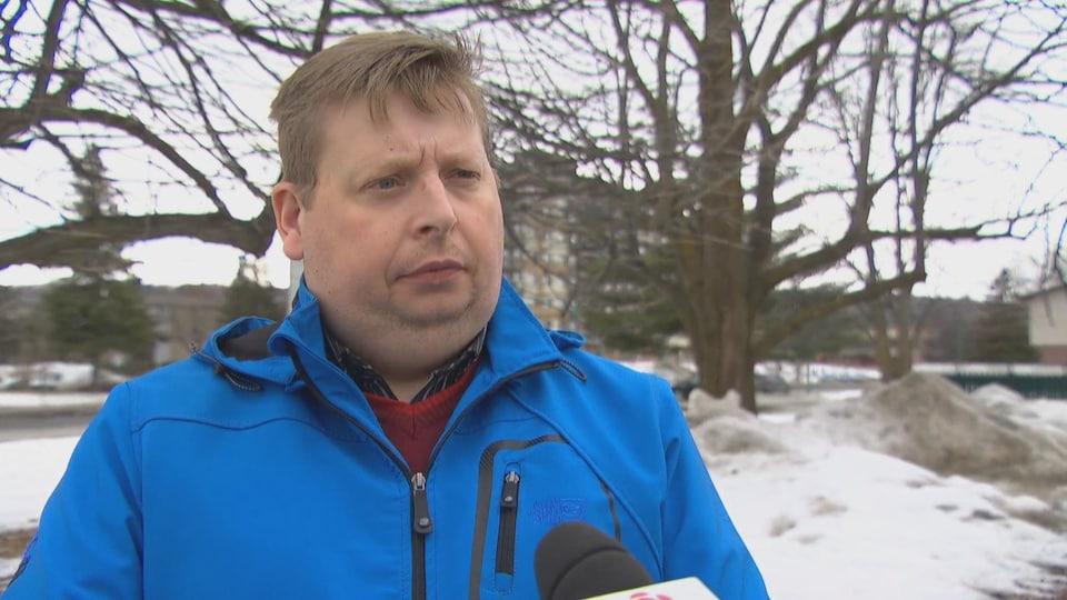 Un homme habillé en manteau d'hiver lors d'une entrevue à l'extérieur au micro de Radio-Canada.