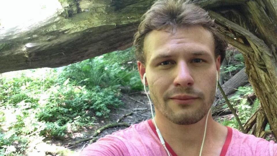 Photo d'un homme dans une forêt avec des écouteurs.