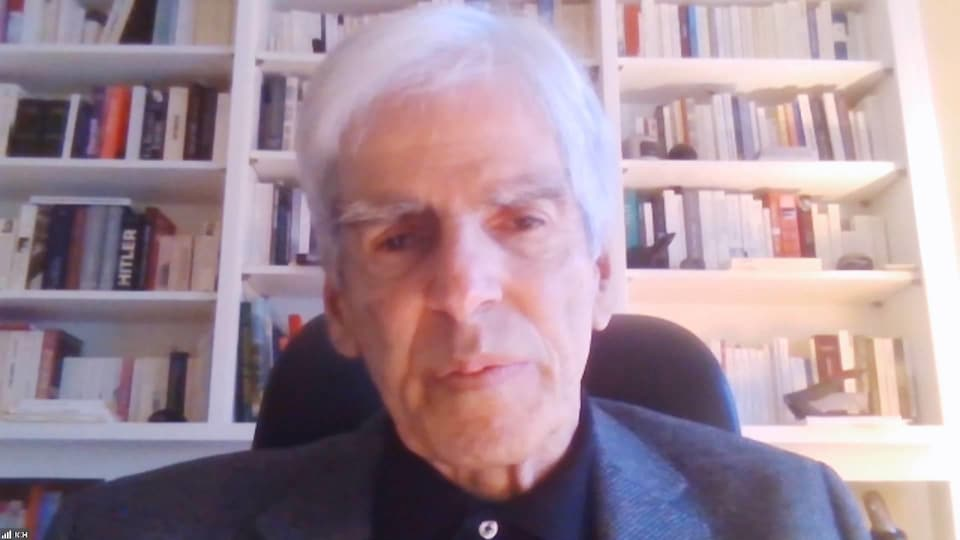 Jean-Claude Hébert en entrevue par webcam devant une haute bibliothèque pleine de livres.