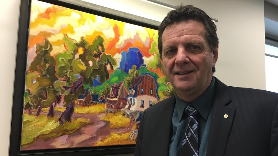 Le président de la Chambre de commerce et d'industrie de Rouyn-Noranda, Jean-Claude Loranger, sourit devant une oeuvre d'art.