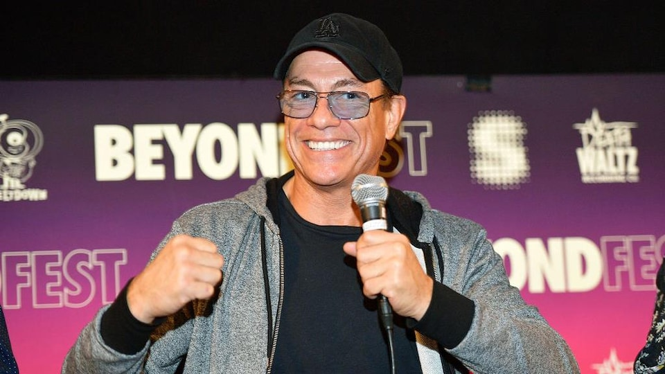 Jean-Claude Van Damme porte une casquette et sourit.