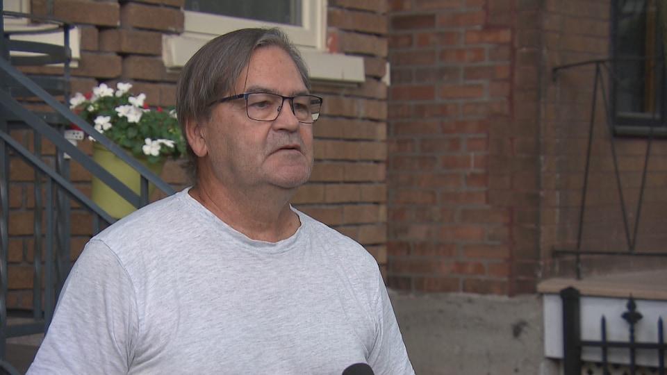 Jean Etcheverry accorde une entrevue à Radio-Canada à l'extérieur d'un immeuble résidentiel de la 4e Avenue, à Québec.