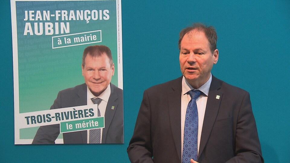 Le candidat Jean-François Aubin, à côté d'une affiche électorale