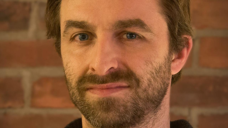 un homme aux cheveux courts et châtains, les yeux bleus foncés, un chandail noir et une fine barbe