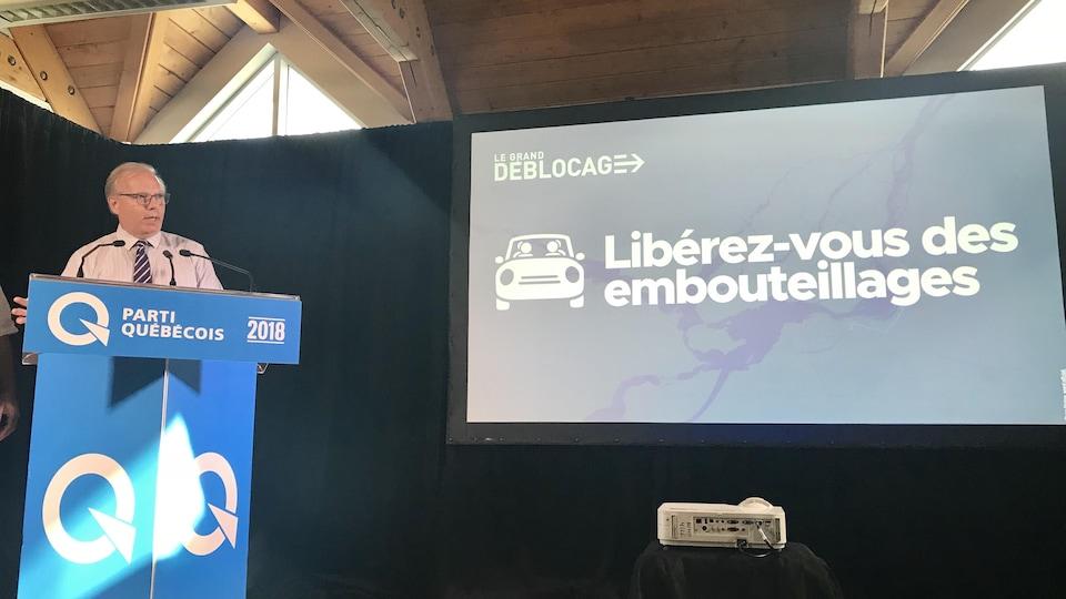 M. Lisée derrière un lutrin. «Libérez-vous des embouteillages», peut-on lire sur un écran à ses côtés.