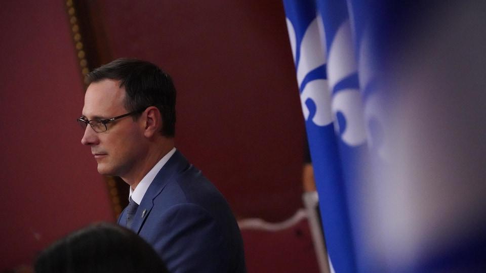 Plan en plongée de Jean-François Roberge devant des drapeaux du Québec.