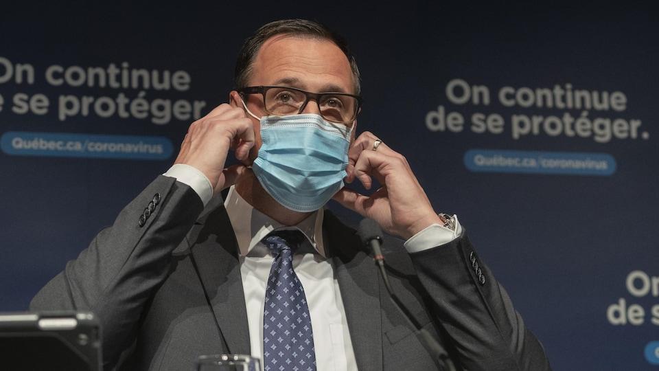Jean-François Roberge s'apprête à enlever son masque avant le début de la conférence de presse.