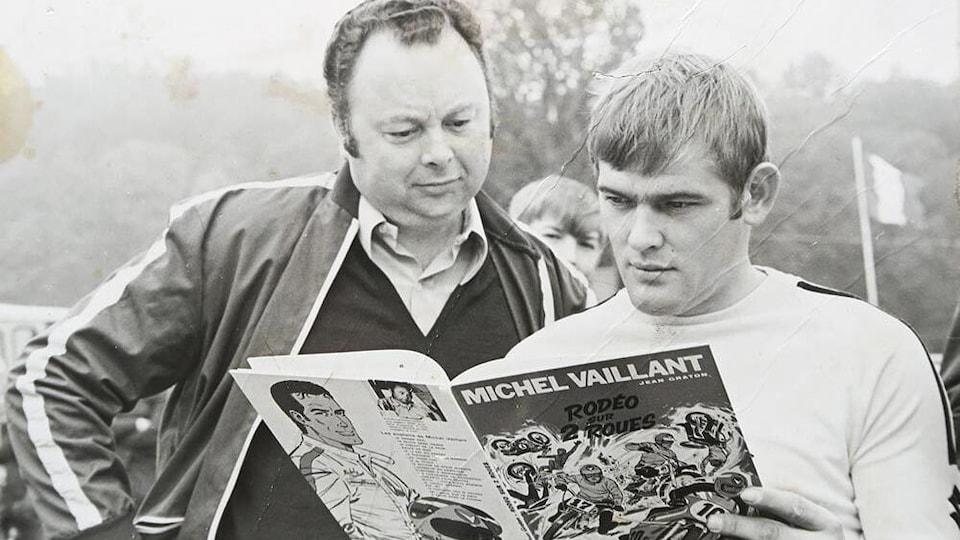 Deux hommes lisent une bande dessinée de Michel Vaillant.