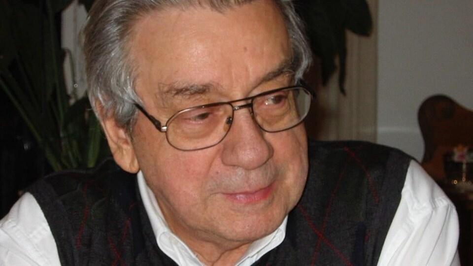 Portrait d'un homme âgé aux cheveux gris qui porte des lunettes.