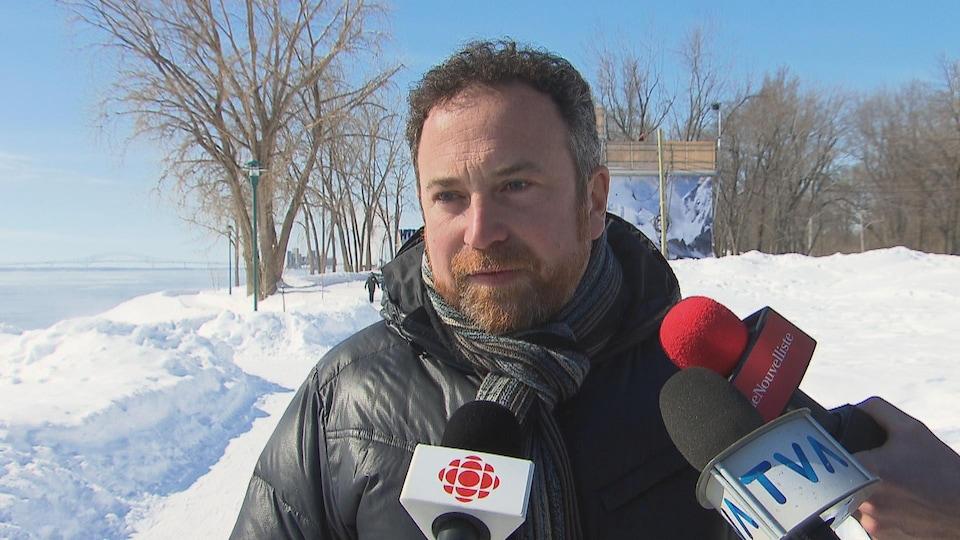 Jean Lamarche à l'île Saint-Quentin l'hiver, devant des micros de journalistes, en mêlée de presse