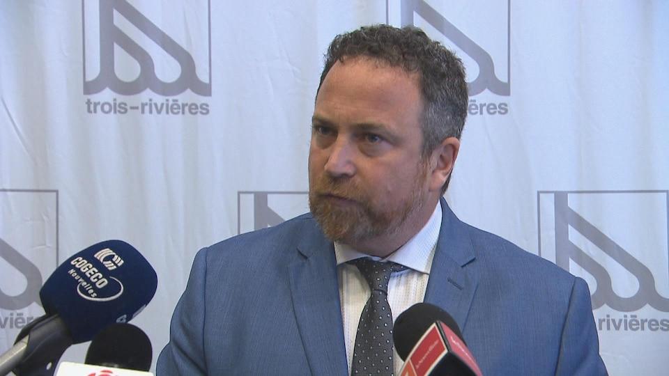 Un homme en veston-cravate devant des micros