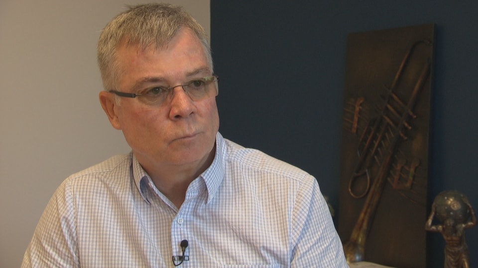 Jean-Claude Bouchard en entrevue avec Radio-Canada dans un bureau.