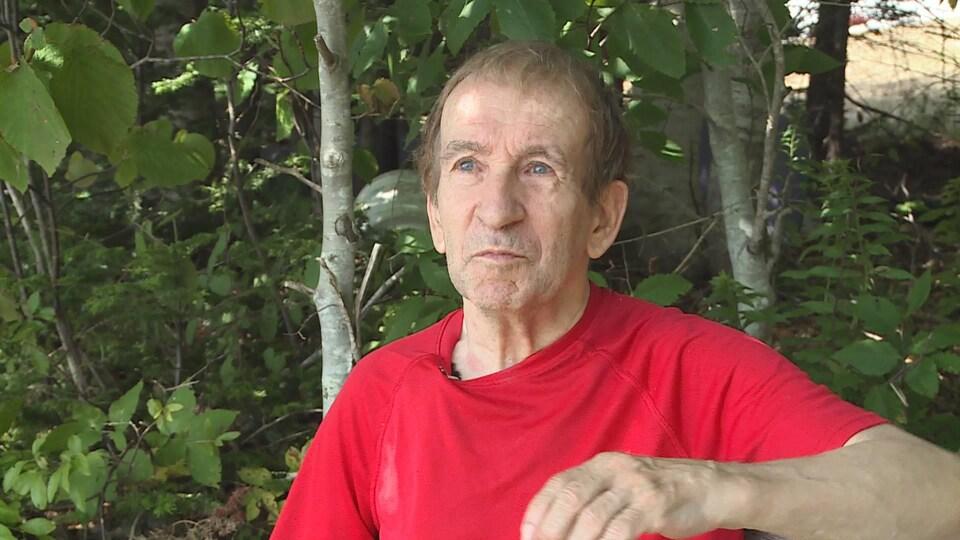 Un homme en chandail rouge assis sur un banc à l'extérieur devant du feuillage. Il regarde au loin dans le néant et a des yeux gris-bleus perçants.