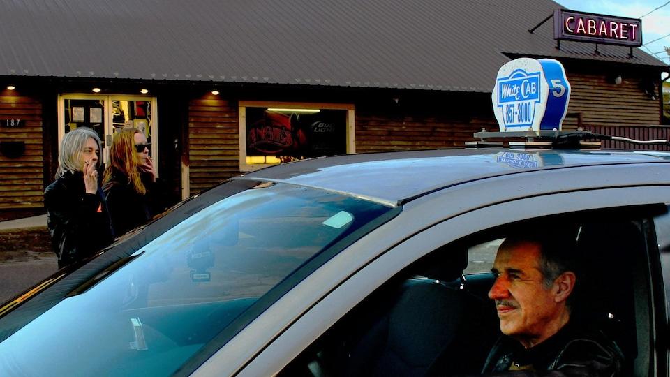 Un homme dans un taxi en face d'un cabaret. Deux femmes fument dehors.