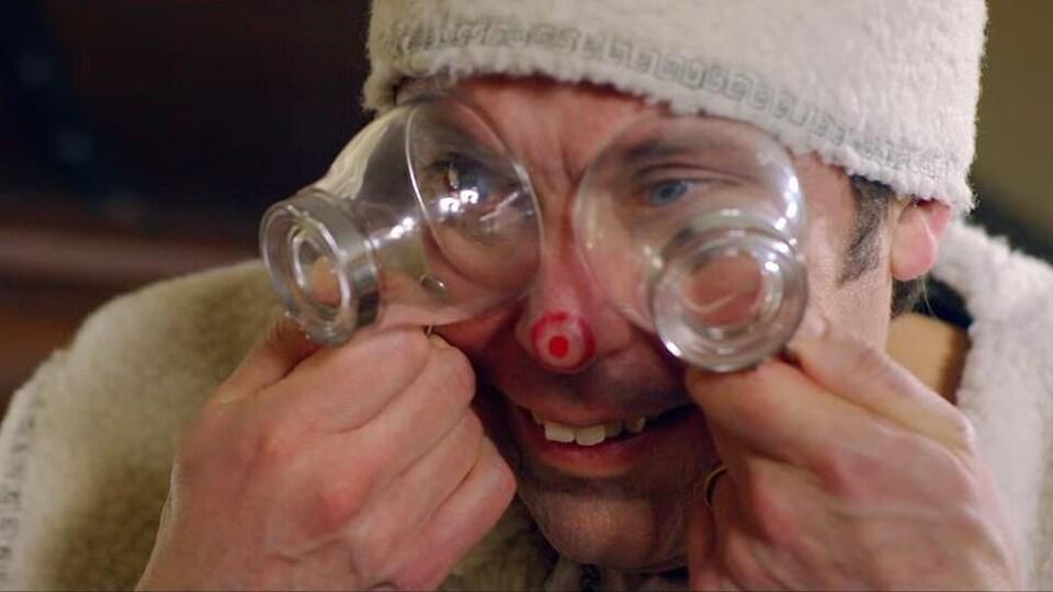 Un homme met deux verres sur ses yeux en souriant.