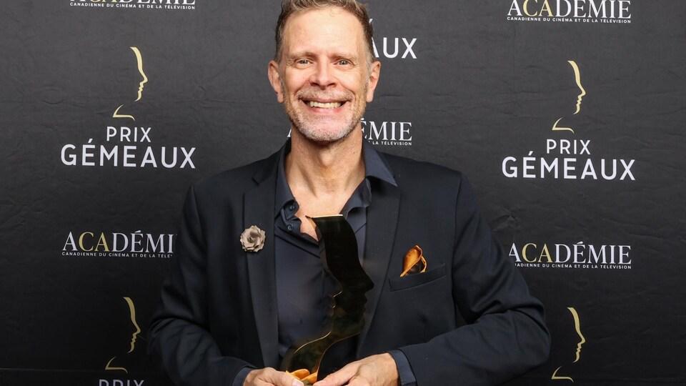 L'homme pose devant un mur avec le logo des Gémeaux et son trophée dans les mains.