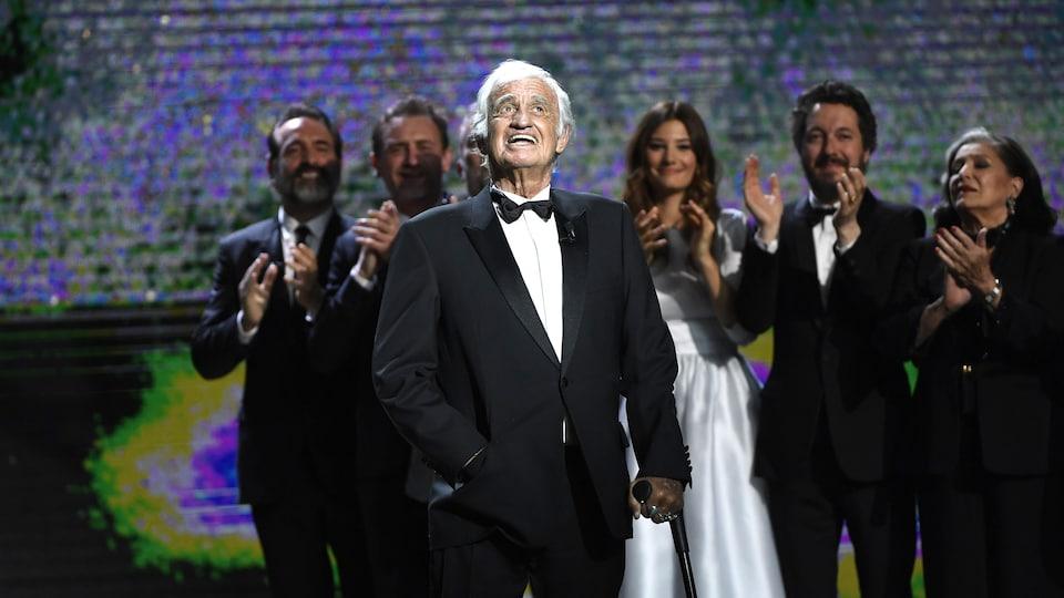 L'acteur se tient sur scène lors de la soirée des César en 2017. Derrière lui, d'autres personnalités applaudissent.