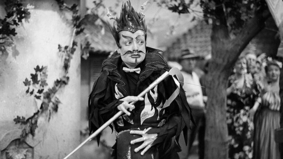 Photo en noir et blanc du ténor, vêtu d'un déguisement orné de flammes et portant une perruque en forme de flammes, marche au milieu d'un décor de village.