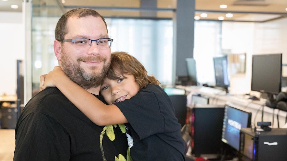 Une photo de Jean-Philippe Blain qui tient son fils Philippe-Alexy dans ses bras. En arrière-plan, une rangée d'ordinateurs est visible.
